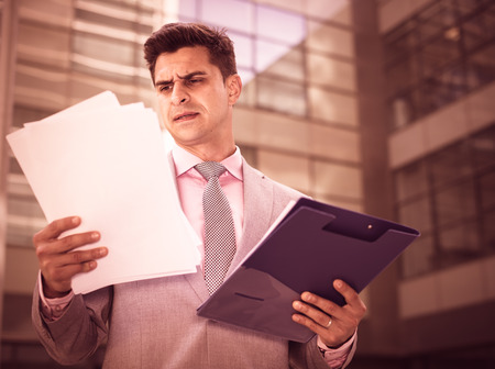 firmeza: Businessman holding folder with documents and attentively reading Foto de archivo