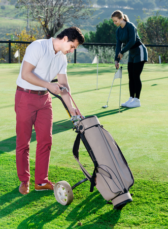 brassy: Man 30-36 years old is choosing right brassy while his partner hits the ball. Stock Photo