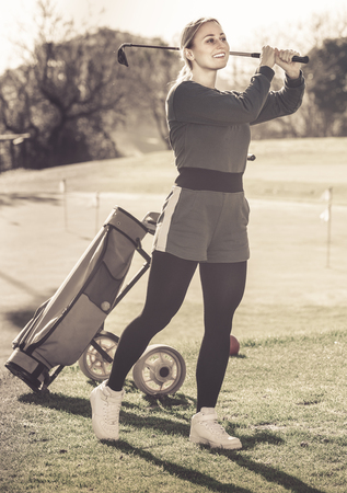 Adult girl looks successfully after the golf game outdoors.