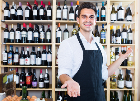 portrait of male seller in apron standing in alcohol section in supermarket