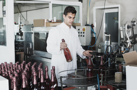 portrait of professional man in white robe working on wine production on manufactory