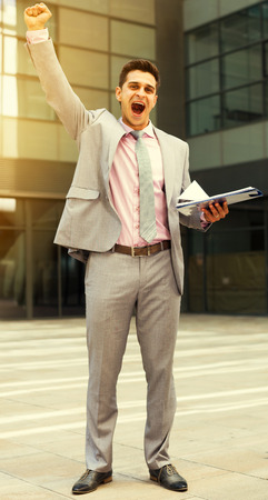 Successful businessman with arm up expressing satisfaction outdoor