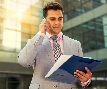 Business man talking on mobile phone outdoors with documents in hand