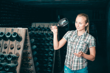 Adult woman holding glass of wine in cellar on winery factory