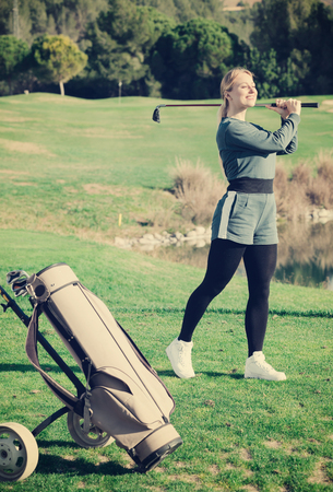 brassy: Woman 25-29 years old is succeeded in ball hitting at golf course.
