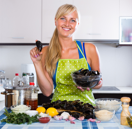 blondie posing with fresh mussels in kitchen