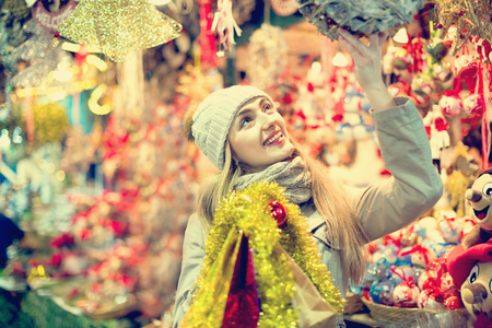 Positive smiling cheerful woman at fair near counter with Christmas gifts in evening time Stock Photo