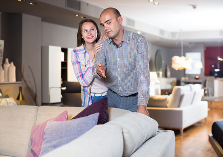 Young couple choosing furniture for apartment in modern home furnishings store