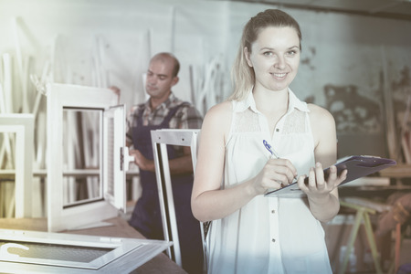 profile measurement: Smiling female supervisor checking quality of work on assembling PVC windows in factory