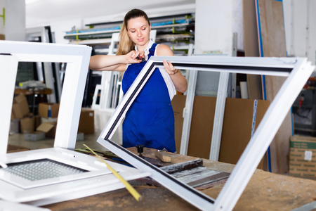 Diligent efficient positive  workwoman assembling PVC window in workshop with manual tools