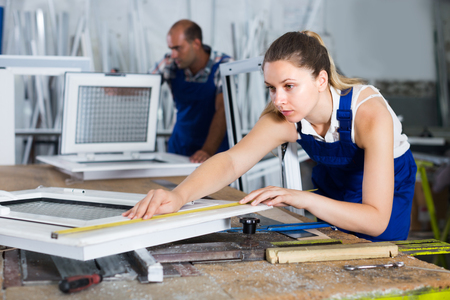 profile measurement: Woman is checking dimensions of finished plastic window using measuring tape at factory. Stock Photo