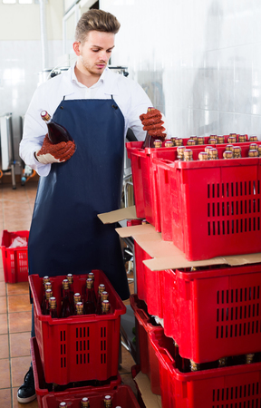 adult european male employee packing wine bottles at sparkling wine factory