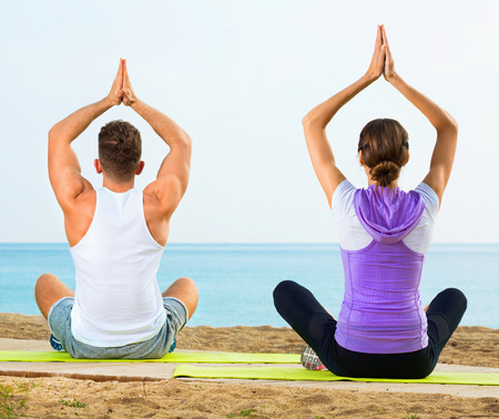 Glad  positive woman and man sitting cross-legged do yoga poses on beach at daytime