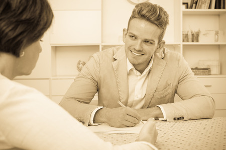 Young handsome man offers woman good bargain Stock Photo