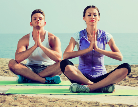 Friendly woman and man sitting cross-legged do yoga poses on beach at daytime
