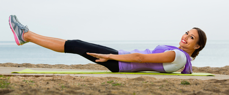 Young smiling cheerful woman doing exercises on beach by ocean at daytime