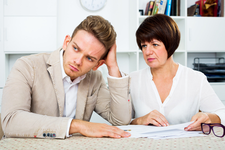 Depressed young man and mature woman sit at table and discuss legal aspects of paperwork. Focus on the man Stock Photo