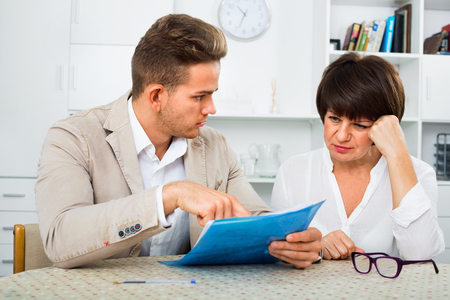 Young diligent handsome man discusses correctness of paperwork with fellow worker