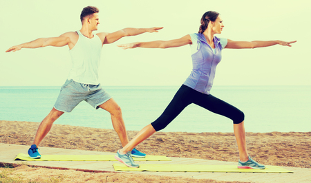 Young cheerful positive smiling couple do exercises on beach by ocean at daytime Stock Photo