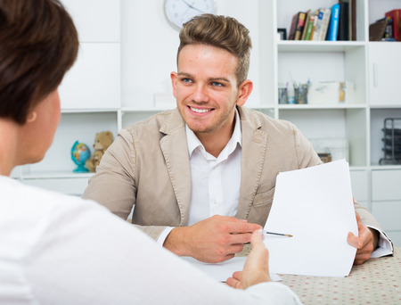 gaining: Young handsome man tells woman about interesting offers of his company Stock Photo
