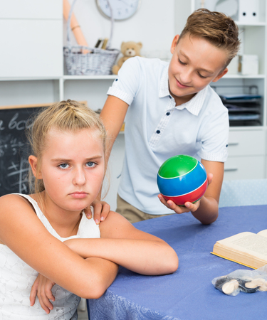 Boy is excusing for the offendedly girl and offering to play ball at home. Stock Photo