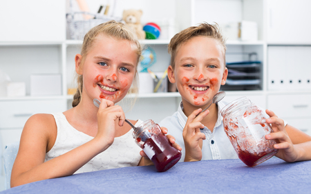 Portrait de s ? ur avec frère qui mangent confiture à déjeuner déjeuner à la maison Banque d'images - 84510093