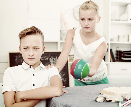 Girl is apologizing to a friend for bad behavior and offering to play ball at home. Stock Photo
