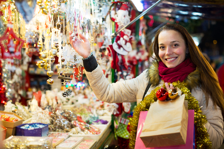 overspending: Portrait of happy adult woman customer near counter with Christmas gifts in evening time