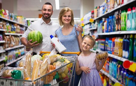 Portrait of smiling american  family standing with full cart in supermarket