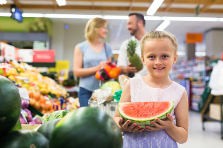 Smiling little girl holding sliced watermelon in fruit section in supermarket