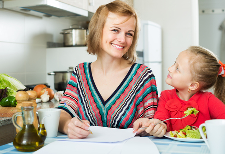 Positive mother working in the kitchen, little girl eating nearby Stock Photo