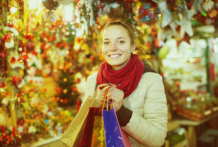 overspending: smiling young woman choosing Christmas decoration at market in evening time Stock Photo