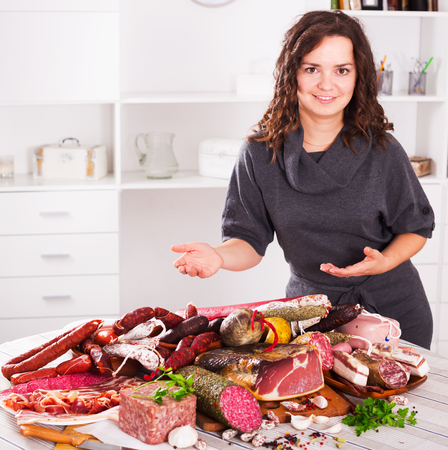 compounding: Beautiful young woman costs near table with smoked products and sausage