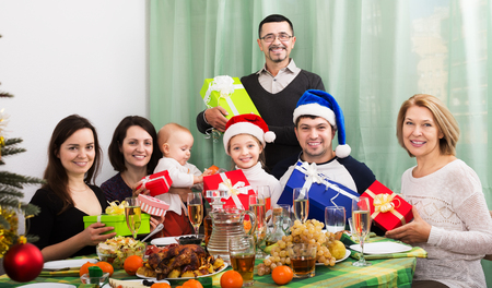 Portrait of happy multigenerational family with gifts sitting at festive Xmas table. Focus on girl