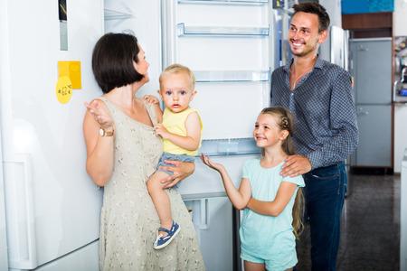 famille avec deux enfants choisissant le nouveau réfrigérateur dans un magasin domestique Banque d'images