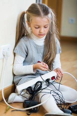 Small girl wearing ponytails playing with electricity and smiling