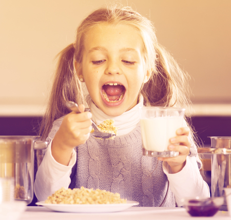 Small girl having breakfast with oatmeal porridge indoors Stock Photo - 84529035
