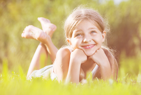 Glad  smiling small girl in elementary school age lying on green grass in park