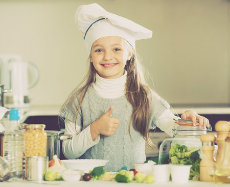 Portrait of sweet little girl with Brussels sprouts and broccoli Stock Photo