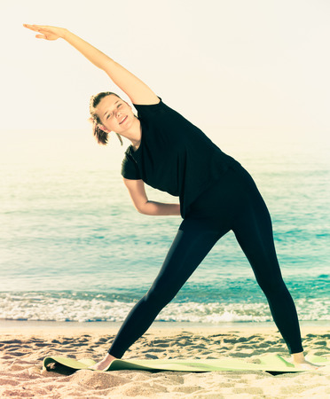 Woman 20-30 years old is practicing stretching in black T-shirt on the beach near sea.