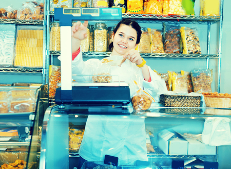 Young female merchant is weighing walnuts in the shop. Stock Photo