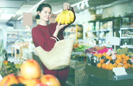 Portrait of smiling young customer selecting bananas in grocery store Stock Photo