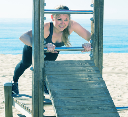 equilibrium: Young smiling woman doing exercises on ocean beach at daytime