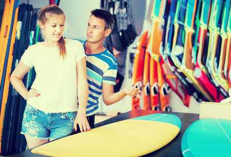 Smiling germany couple is choosing surfboard in nautical shop.