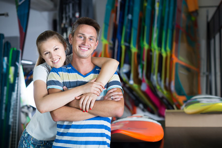 Happy couple is choosing colorful boards in store on the beach