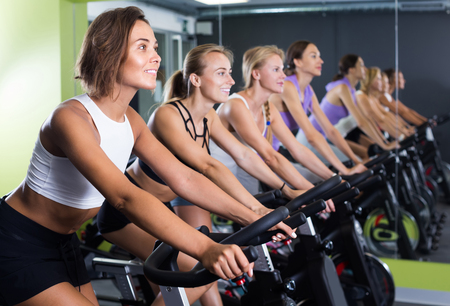 Sporty belgian women on cardio training on exercycles in health club
