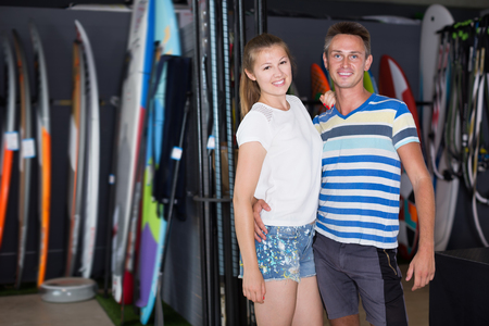 Portrait of glad couple who is buying surfboard in nautical shop