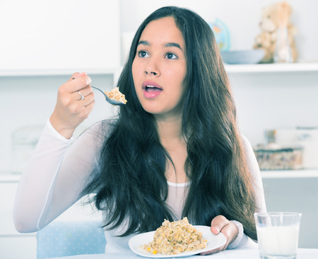 brazilian ethnicity: Young smiling girl eating tasty mixture of cereals sitting on the table Stock Photo