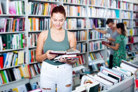 Pretty teenager girl holding open book in hands and looking at it in store