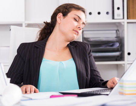 expertize: Female trainee is sleeping at work after putting the reports in the office. Stock Photo